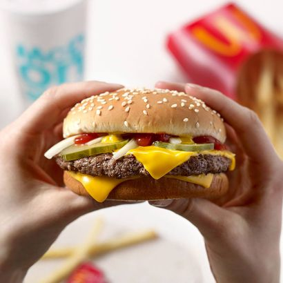 Hands holding a McDonald's cheeseburger