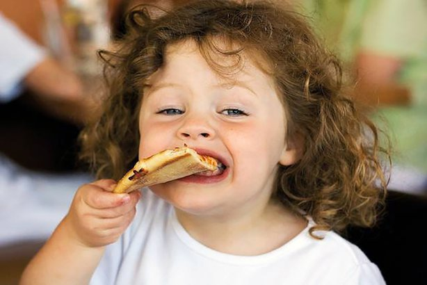 Kid eating a slice of pizza