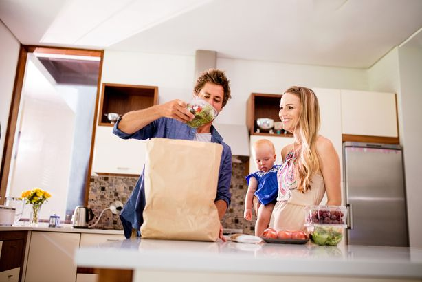 Man unloading a grocery bag at home next to his wife and baby