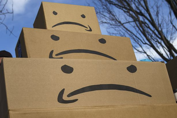 boxes with the Amazon logo turned into a frown face are stacked up