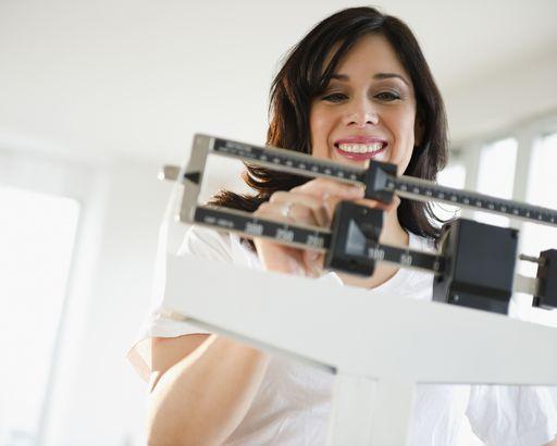 smiling hispanic woman weighing herself on scale