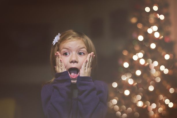 young girl excited in front Christmas tree
