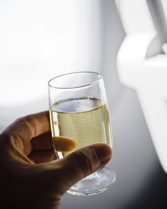 hand holding champagne glass in airplane, close-up