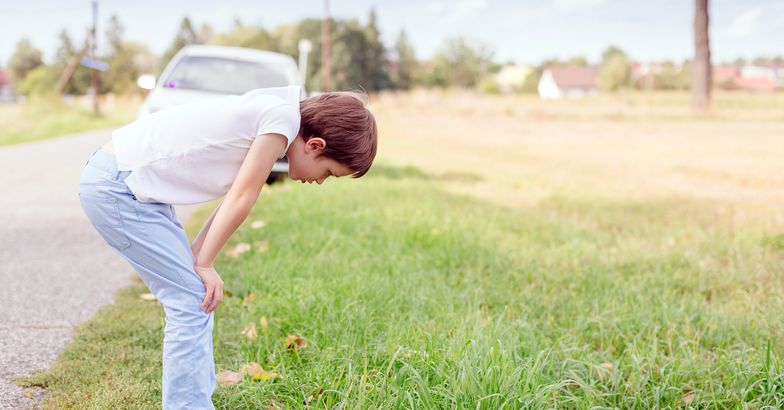 boy with motion sickness leaning over in grass