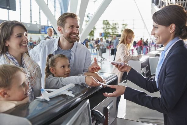 customer service representative helping family checking in with tickets at airport check-in counter