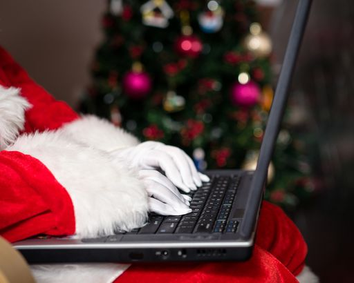 30305f6ba8 midsection of Santa Claus using laptop during Christmas