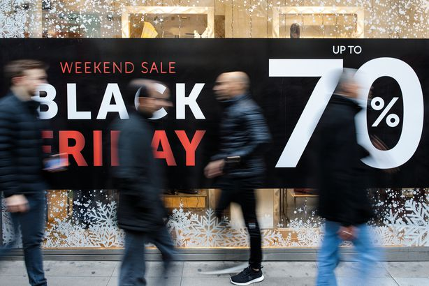 shoppers walk past a Black Friday sale sign