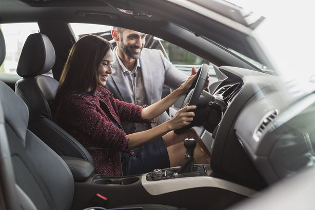 car salesman and female customer in driver's seat of new car in car dealership showroom