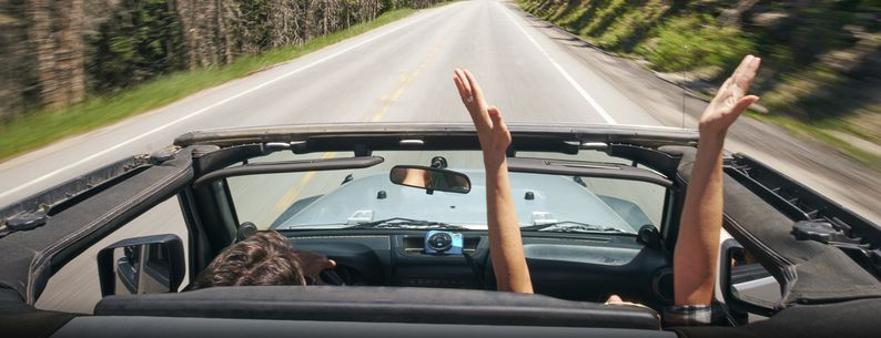 road trip couple driving convertible on rural highway with hands raised, Breckenridge, Colorado