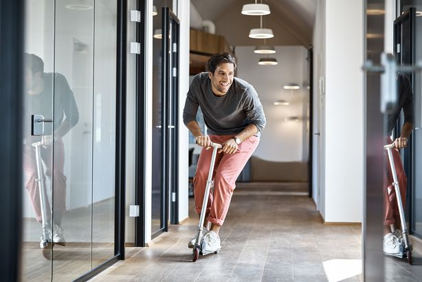 businessman enjoying on push scooter in office