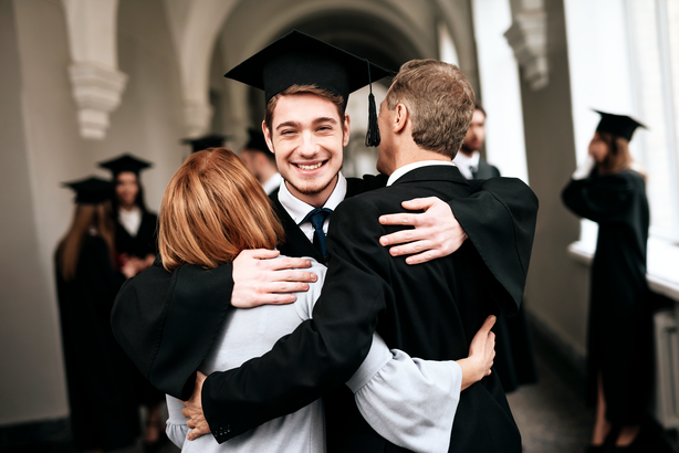 Happy graduate hugging his parents