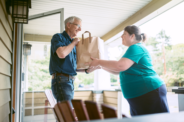 Neighbor bringing groceries to an elderly man
