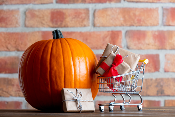 Pumpkin in front of a brick wall with a miniature shopping cart and presents