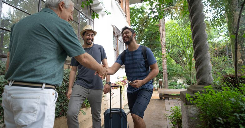 Senior man welcoming two younger men to rent his home