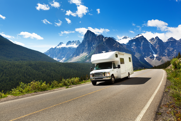 RV on the open road with mountains in the background