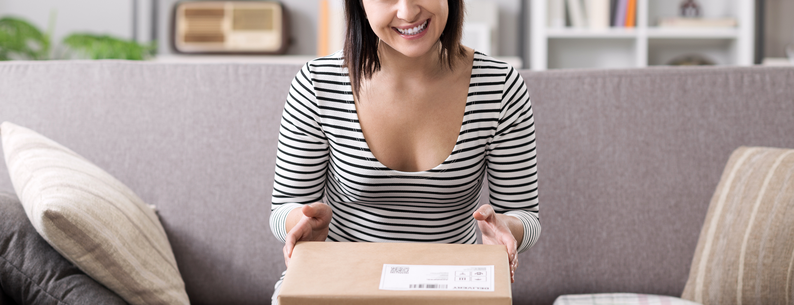 Woman sitting on her couch at home opening a package