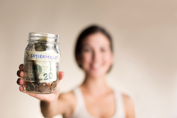 Woman holding a retirement jar with money in it