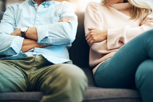 Couple getting a divorce sitting separate on a couch