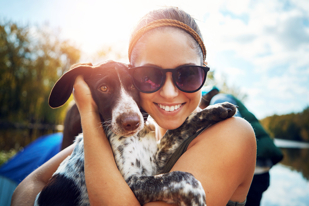 Woman smiling and holding her dog outside in the sunshine