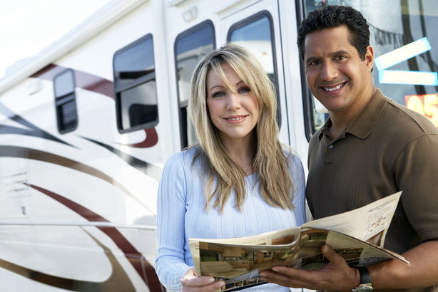 Couple looking at a brochure interested in renting or purchasing an RV