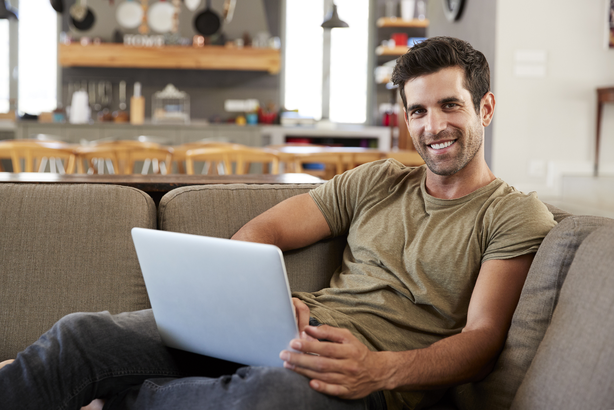 Smiling man working on his laptop from his couch