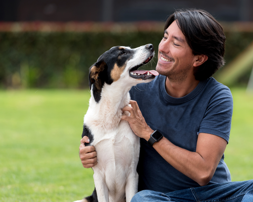 Man sitting outside smiling and holding his dog