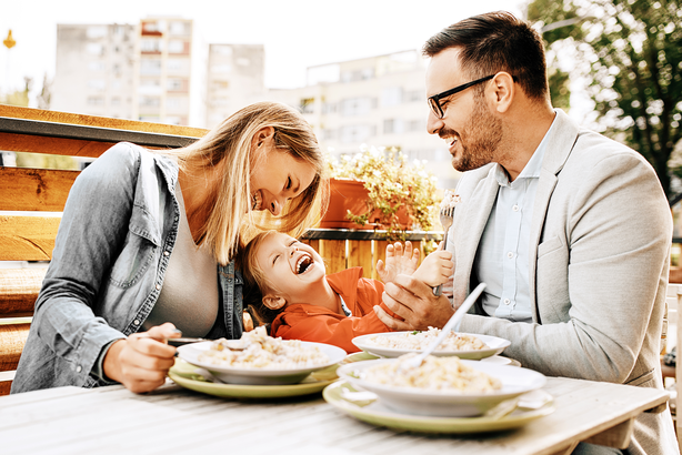 Happy family having a meal outside at a restaurant