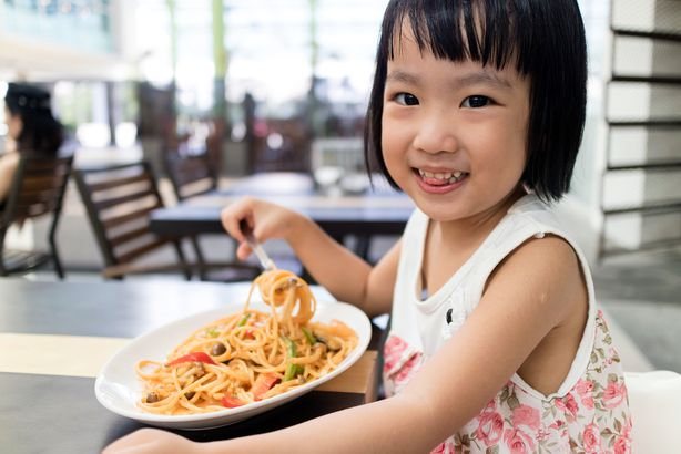 Little girl eating noodles at a restaurant
