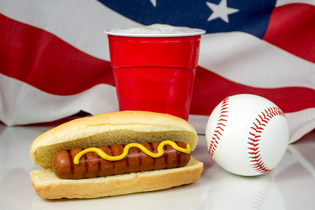Hot dog and a beer next to a baseball with an American flag in the background