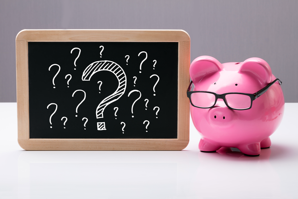 Piggy bank wearing glasses next to a chalkboard with question marks