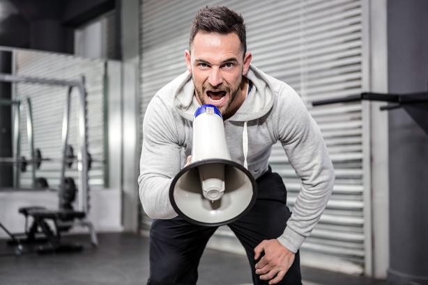 Personal trainer yelling into a megaphone