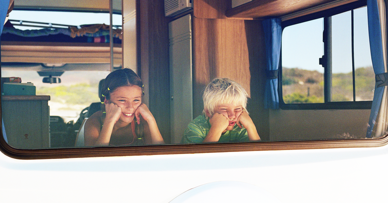 two children looking out back window of rv