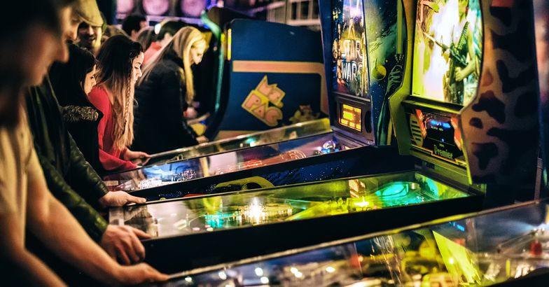 People playing pinball machines