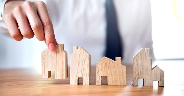 Hand of businessman choosing house model