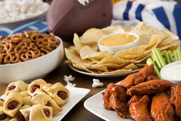Tailgating snacks including hot wings, pigs in a blanket, queso, and chips