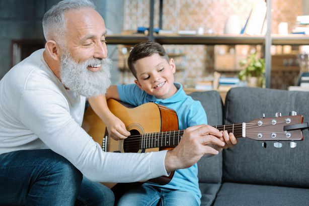 Grandpa teaching his grandson how to play guitar