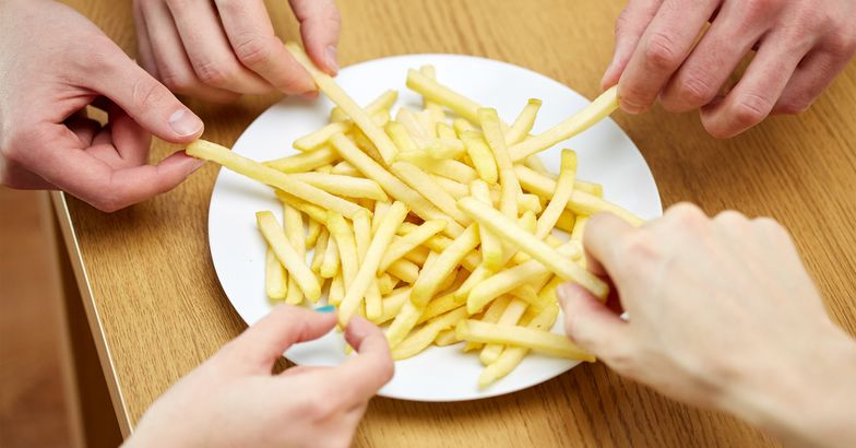 Close up of hands taking french fries from plate