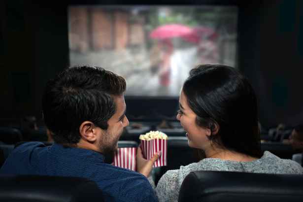 Couple watching a movie in a theater with popcorn