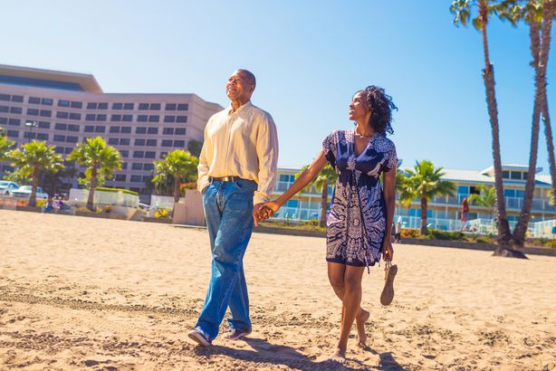 Older couple walking on the beach in front of a resort