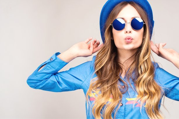 Cool hipster woman wearing blue sunglasses