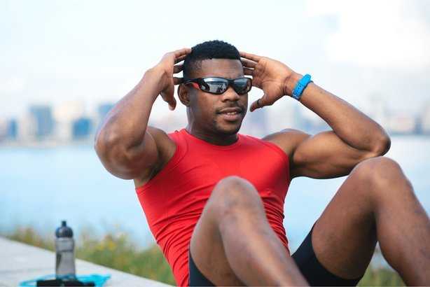 a770ad77e1 African American man doing crunches outside wearing sunglasses