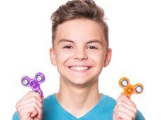 Young teen boy holding popular fidget spinner toy