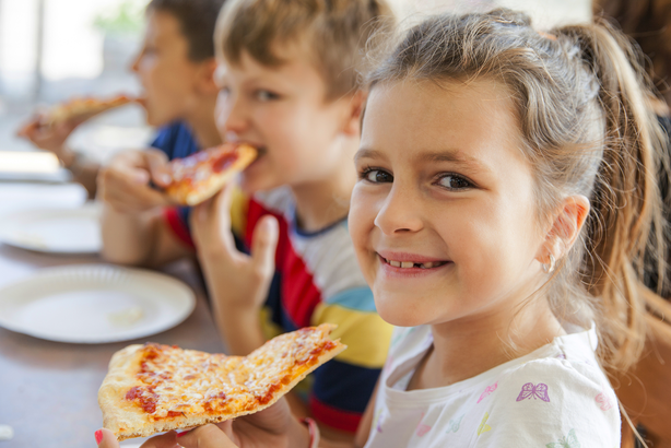 Young children eating pizza in a restaurant