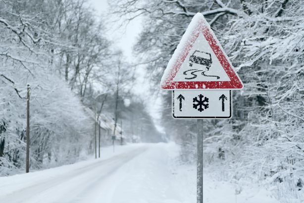Icy road warning sign on a snowy road