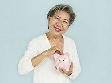 asian grandmother putting money into a piggy bank