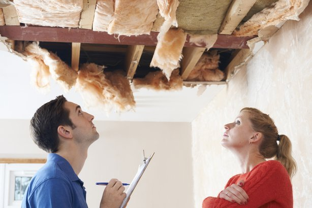 repairman with clipboard inspecting ceiling damage while concerned woman talks on phone