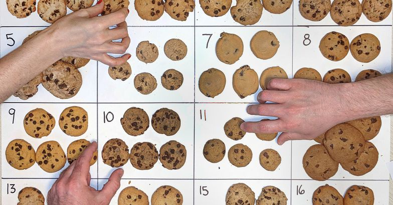 chocolate chip cookies laid out and numbered on posterboard, hands reaching for cookies