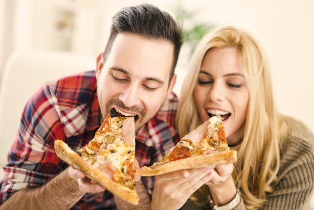 happy couple eating slices of pizza