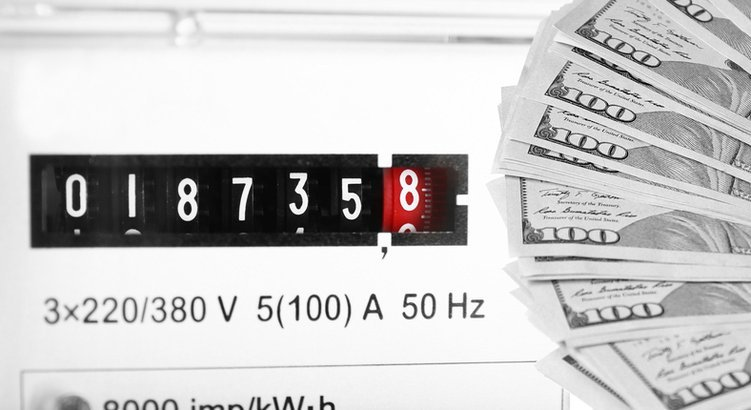 household electricity meter accompanied by a stack of hundred dollar bills