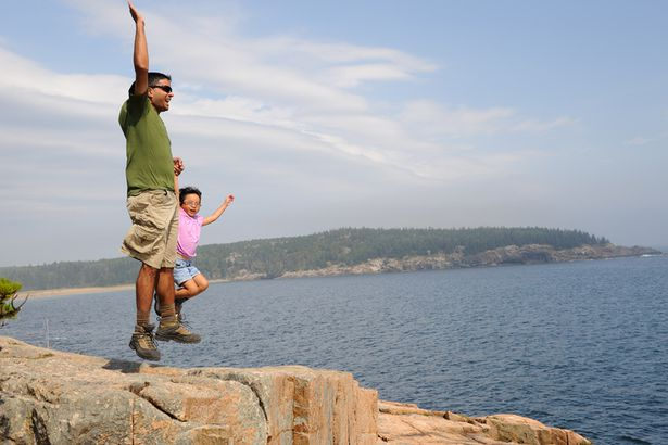 Family jumping for joy in Acadia